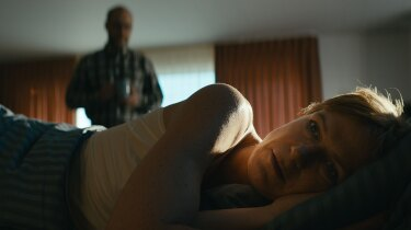 "Anna lays in bed with her back against her husband. | Still from ""Follow the Money"" Season 3, Episode 5"