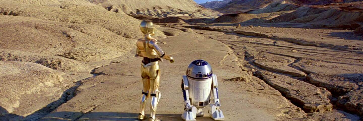 """C-3PO and R2-D2 walk toward Jabba's Palace, which was filmed in Death Valley's Twenty Mule Team Canyon for this scene in """"Episode VI: Return of the Jedi."""" Lucasfilm, LTD."""