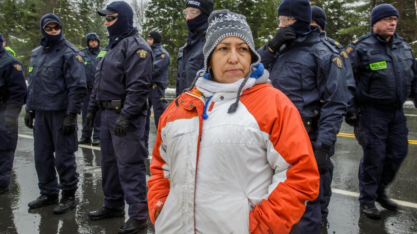 A woman stands in front of a line of police officials.