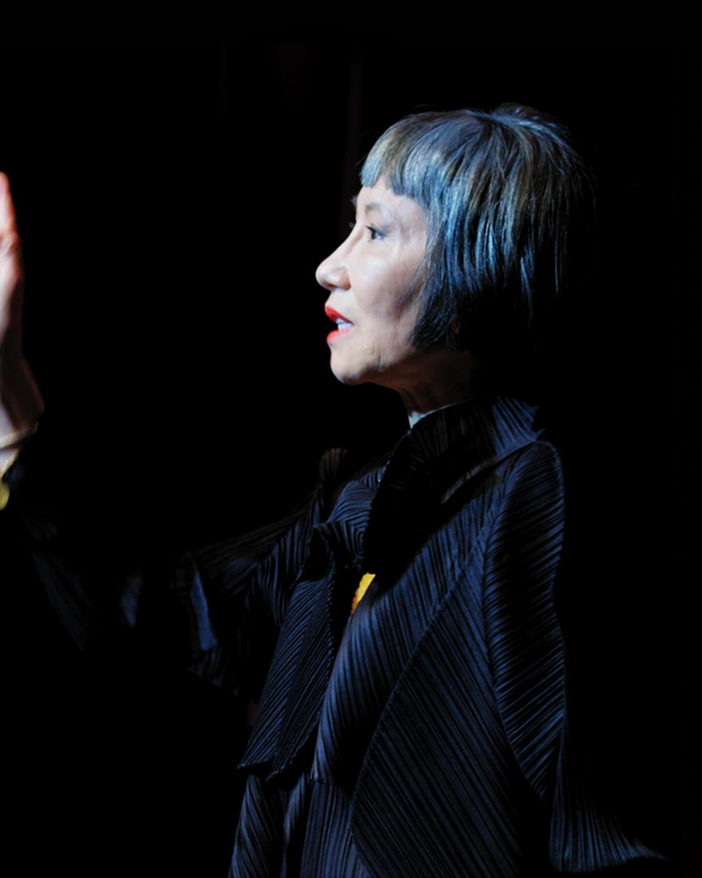 Amy Tan holds her hand up.