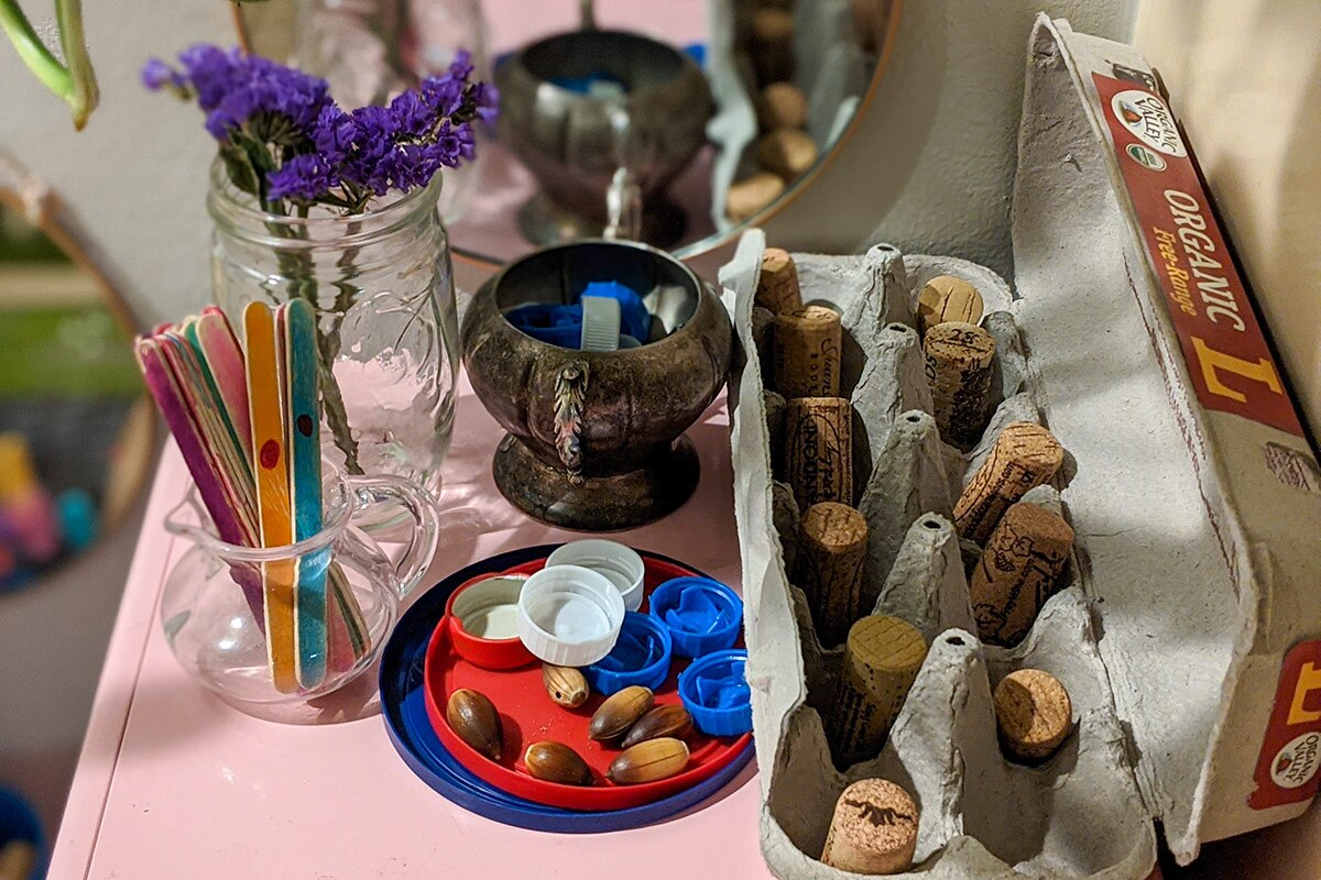 Loose parts including popsicle sticks, bottle caps, pieces or cork, empty egg cartons, and more are arranged on a pink table.