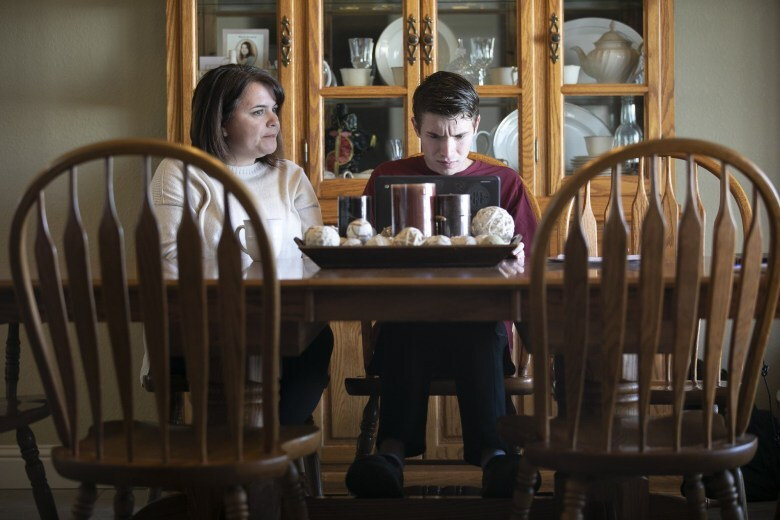 Daniel and his mother, Linda, sit at their dining room table. Daniel's brow is furrowed as he looks down at a black laptop. His mother sits next to him.