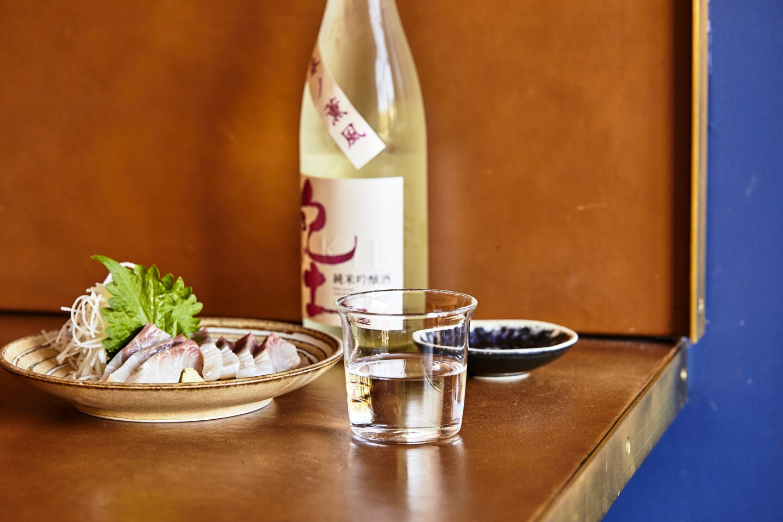 A cup of ginjo sake paired with Tsubaki's kanpachi sashimi.