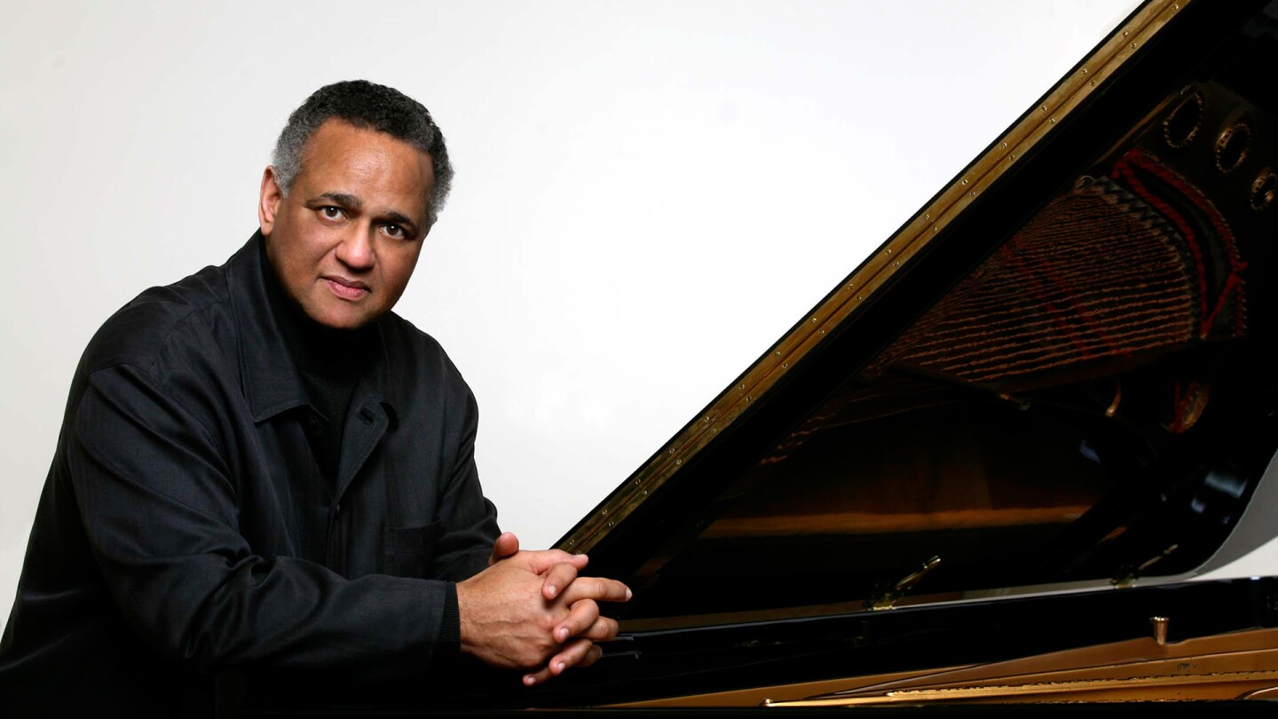 A publicity shot of André Watts sitting by a piano | Courtesy of Pacific Symphony