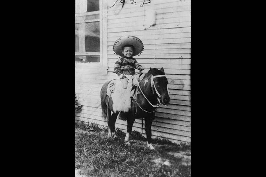 Black and white photo of a young boy in a sombrero sitting on a pony