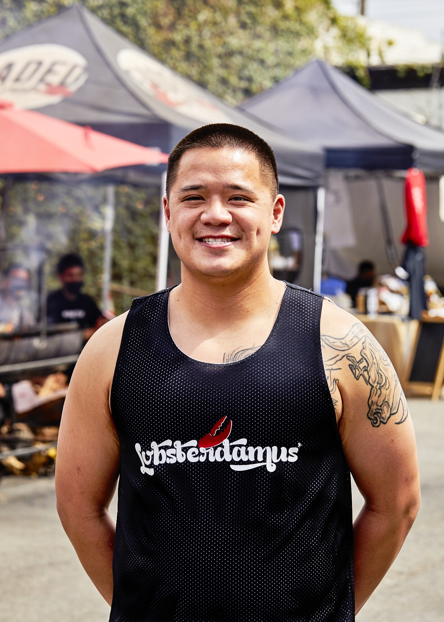 """Francis Reyes, co-owner of Lobsterdamus and Mano Po, poses at the FilLed Market. He's wearing a black tank top that reads, """"Lobsterdamus,"""" with his arms behind his back."""