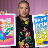 """Julio Salgado is wearing a floral print shirt and a black jacket while holding up two pieces of his art on each hand. The artwork on his left features the side profile of a woman with multicolored hair and statements like, """"Black Lives Matter,"""" """"#MeToo,"""" """"Make Love Not War,"""" and """"Thank Black and Brown Trans Women for Pride."""" The artwork on the right reads, """"No Longer Interested in Convincing You of My Humanity,"""" with a graduation cap at the bottom. Salgado is standing in front of a pink background."""