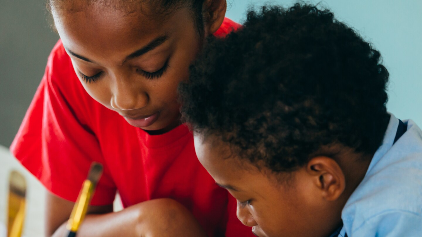 Two Black children lean into something they are working on on a table with paintbrushes and crayons.