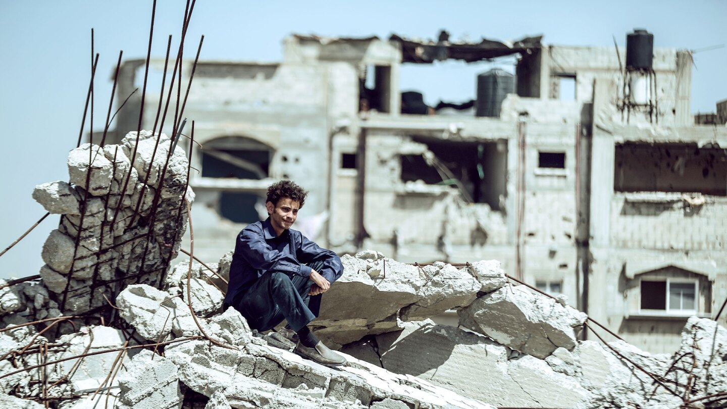 "A young Palestinian man sitting atop rubble. | ""Idol""/ Kino Lorber"