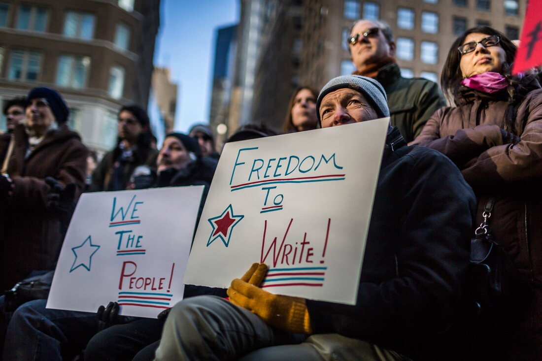 A protester holding a placard that writes ' Freedom to Write!'