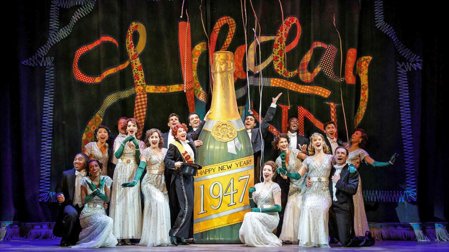 "Stage performers gather to pose onstage next to a large cardboard cutout of champagne labeled ""Happy New Year: 1947."" 