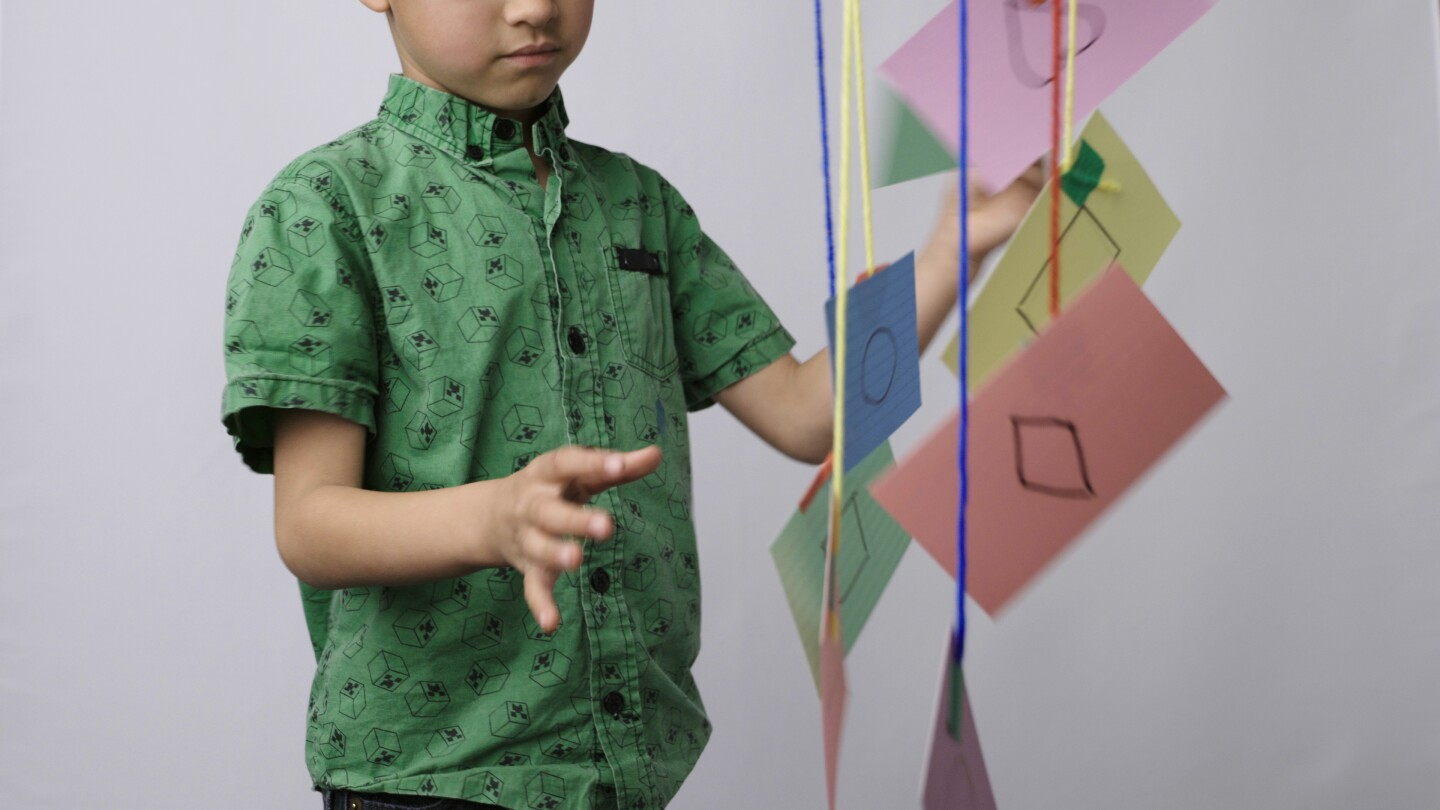 Child interacts with a shape mobile