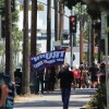 "Man with ""Trump 2020"" flag walks down street, towards other protestors on May 1 in Downtown L.A. 