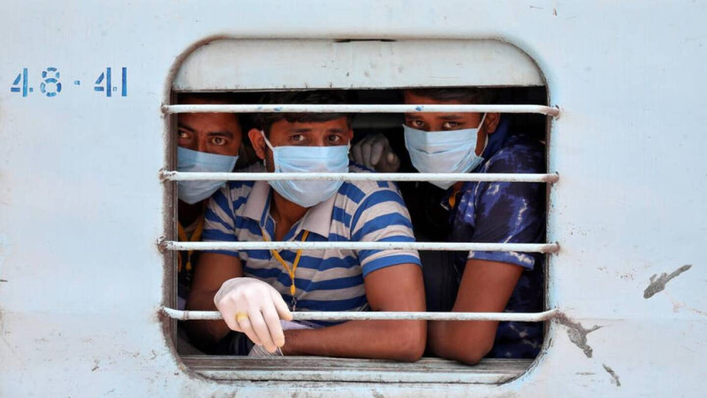 FILE PHOTO: Migrant workers, who were stranded in the western state of Rajasthan due to a lockdown imposed by the government to prevent the spread of coronavirus disease (COVID-19), wear protective masks as they look out from a window of a train
