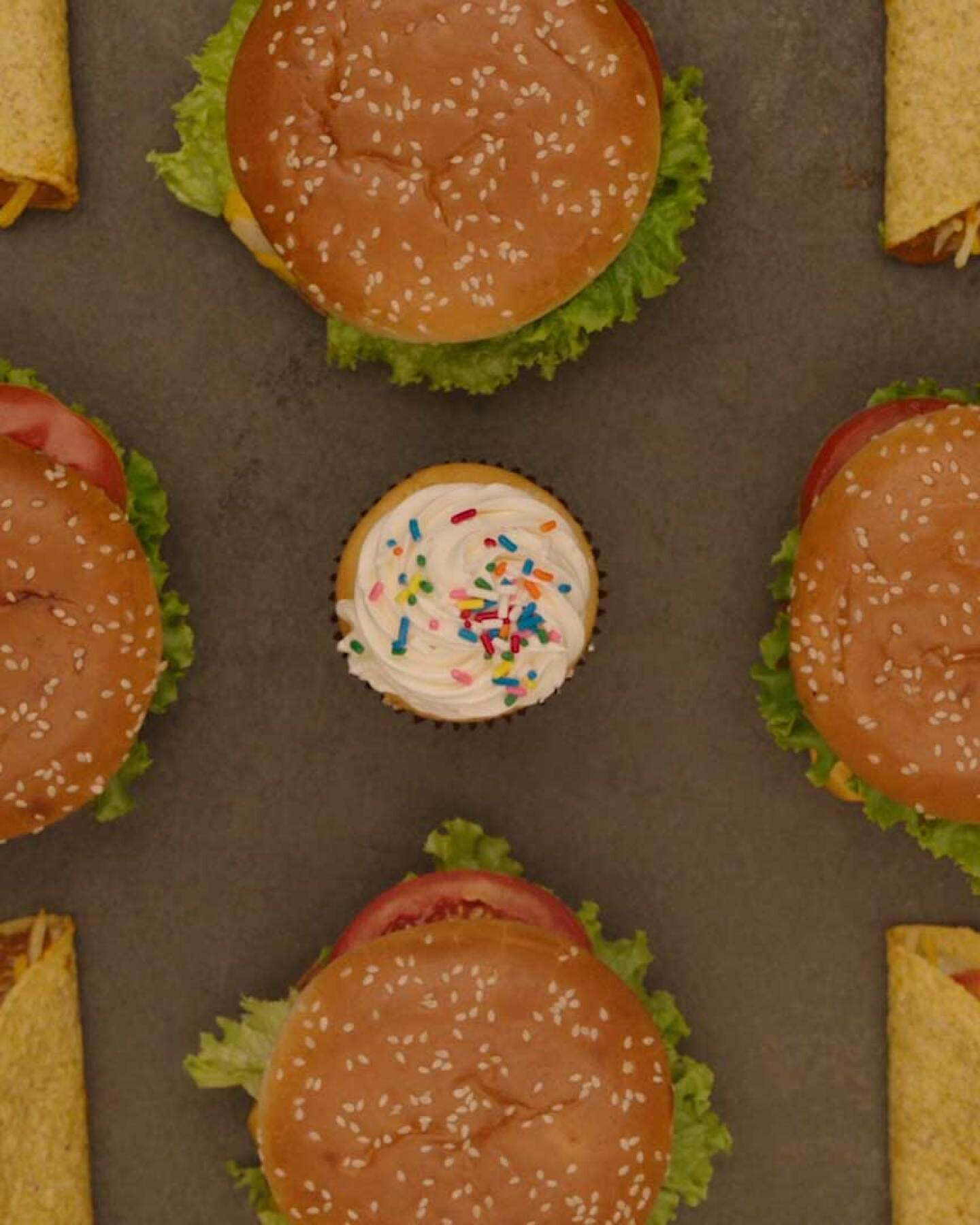 """A styled photo of hamburgers, fries, popcorn and tacos 