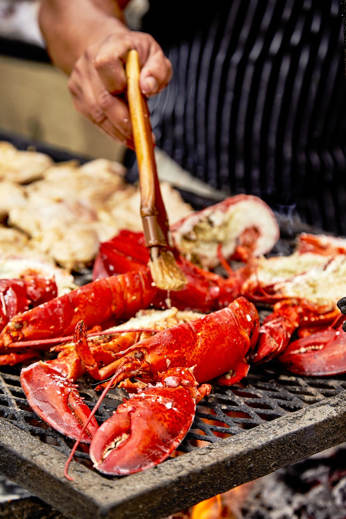 A close-up shot of Johnny Angeles of Lobsterdamus butters up lobster at the FilLed Market.