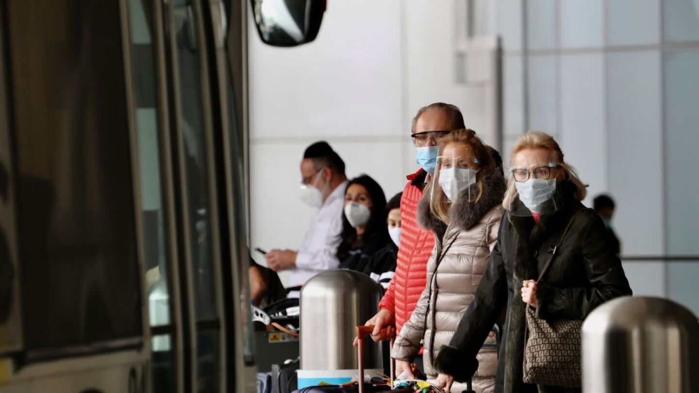 Travelers with face masks wait for public transportation services at the International Airport in Los Angeles, California, on Feb. 1, 2021.