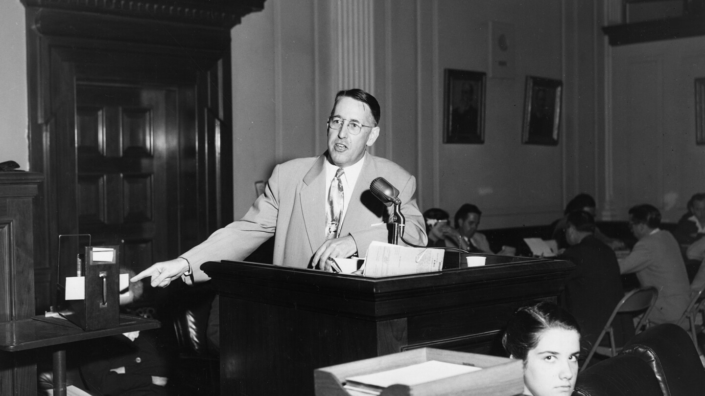 """Chairman Charley Johns speaks at a podium with people sitting beside tables behind and in front of him. 