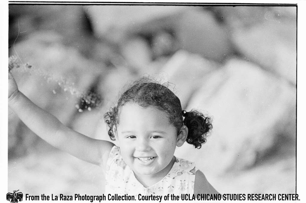 CSRC_LaRaza_B16F6C10_Staff_032 Young girl at the beach | La Raza photograph collection. Courtesy of UCLA Chicano Studies Research Center