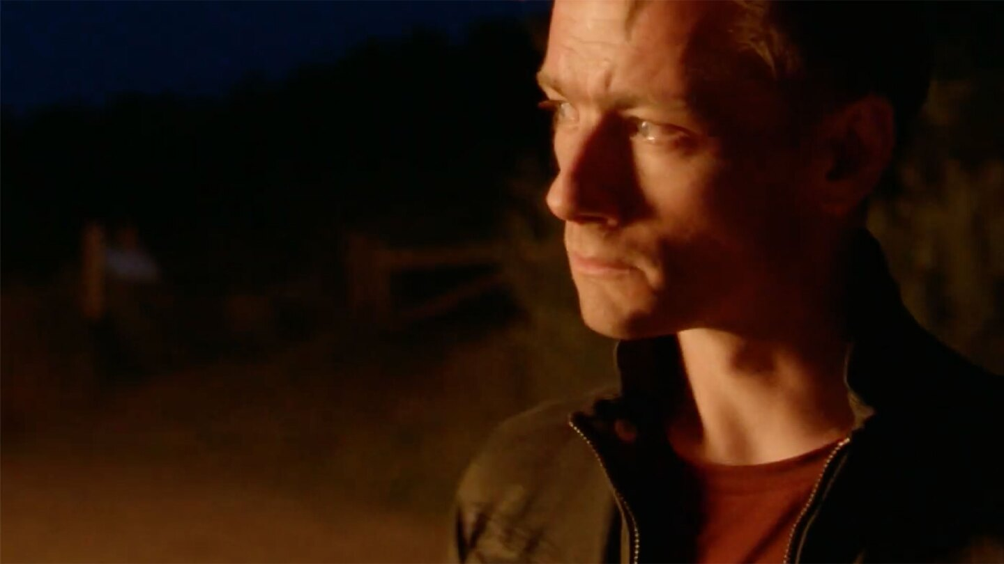 "Man's concerned face lit by golden light to his right. | Still from ""Follow the Money"" Season 3"