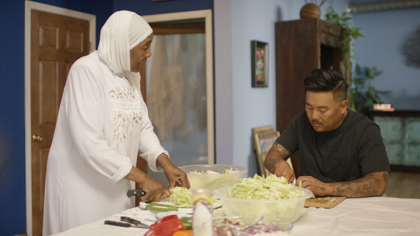"""Led by activist Aqeela Sherrills, Roy visits with Sherrills' mother as she prepares free food for the community in """"Watts""""."""