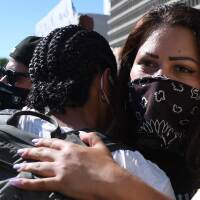 Protestors hug at the Brown Unity March, which was organized to unite the Black, Latino and Indigenous communities in demanding justice for victims of police brutality in Los Angeles. | ROBYN BECK/AFP via Getty Images