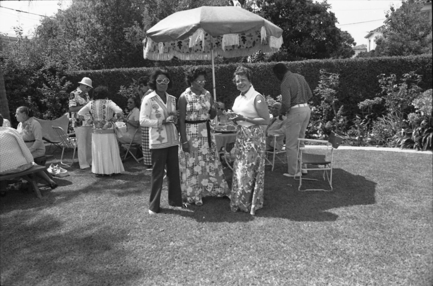 Men and women talking at a backyard garden party in Oakland, circa 1970s. | Oakland Public Library Digital Collections