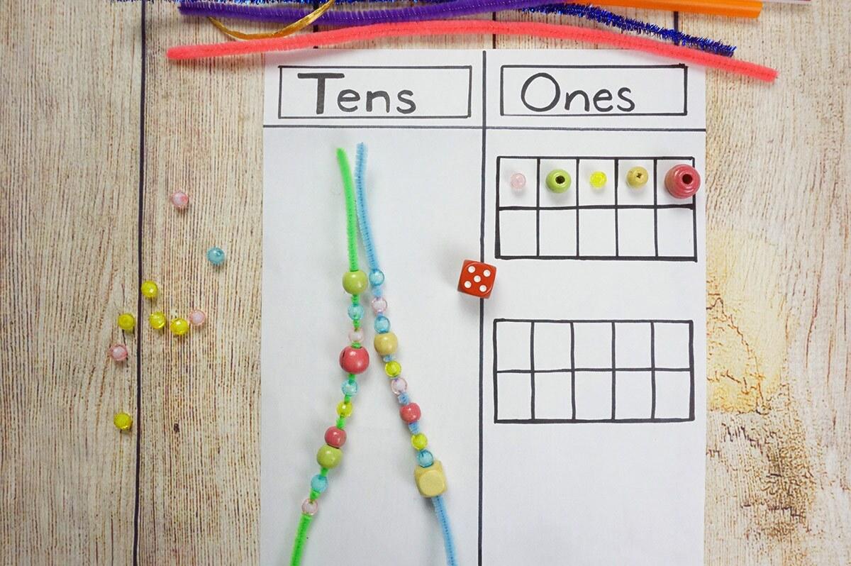 """Una hoja de papel dividida en dos columnas con los títulos """"decenas"""" y """"unidades"""" con cuentitas, limpiapipas, trozos de hilo y un marcador encima."""