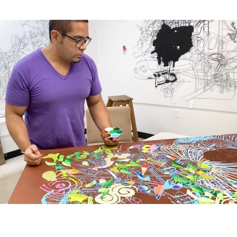 David Rios holds his paint and brush over an abstract piece of art.