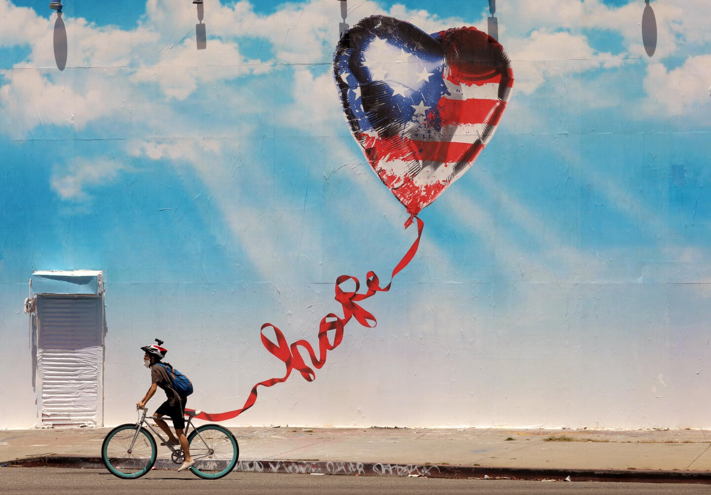 """A bicyclist wearing a face mask rides past a mural depicting a heart-shaped balloon patterned like the American flag flying in a blue sky. The balloon's string is twisted to read """"hope."""""""