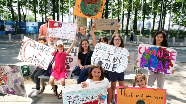A group of young climate activists hold up signs about climate change.