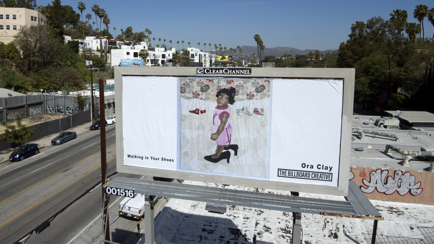 Fiber artist Ora Clay's billboard is located along Sunset Blvd. and shows a young, Black girl in a pink dress wearing a pair of black heels that are too big for her.