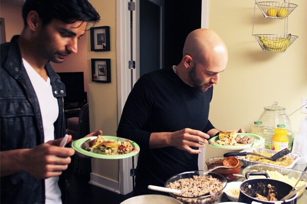 Jason Velazquez (right), a revert, samples traditional foods with his husband, Tony Follo (left) I Photo: Jonathan Olivares