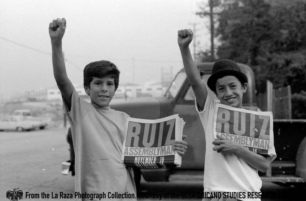 CSRC_LaRaza_B14F11S4_N012 Young boys raise their fists while holding newspapers in support of Raul Ruiz for California's 48th State Assembly District | Manuel Barrera Jr., La Raza photograph collection. Courtesy of UCLA Chicano Studies Research Center