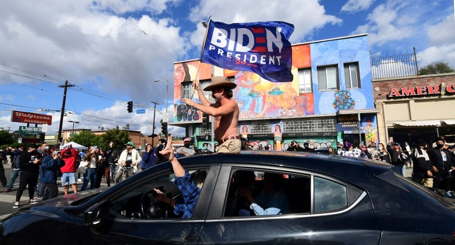 A man waves a Biden flag from his car as people take to the streets in Los Angeles on Nov. 7, 2020 to celebrate Joe Biden and the Democratic Party's victory in the 2020 presidential election. | Frederic J. Brown/AFP via Getty Images