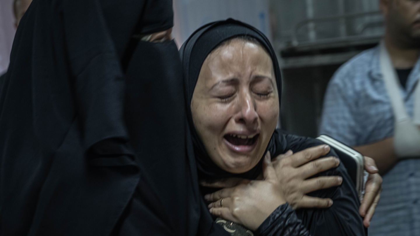 A woman cries out in anguish as another person comforts her.
