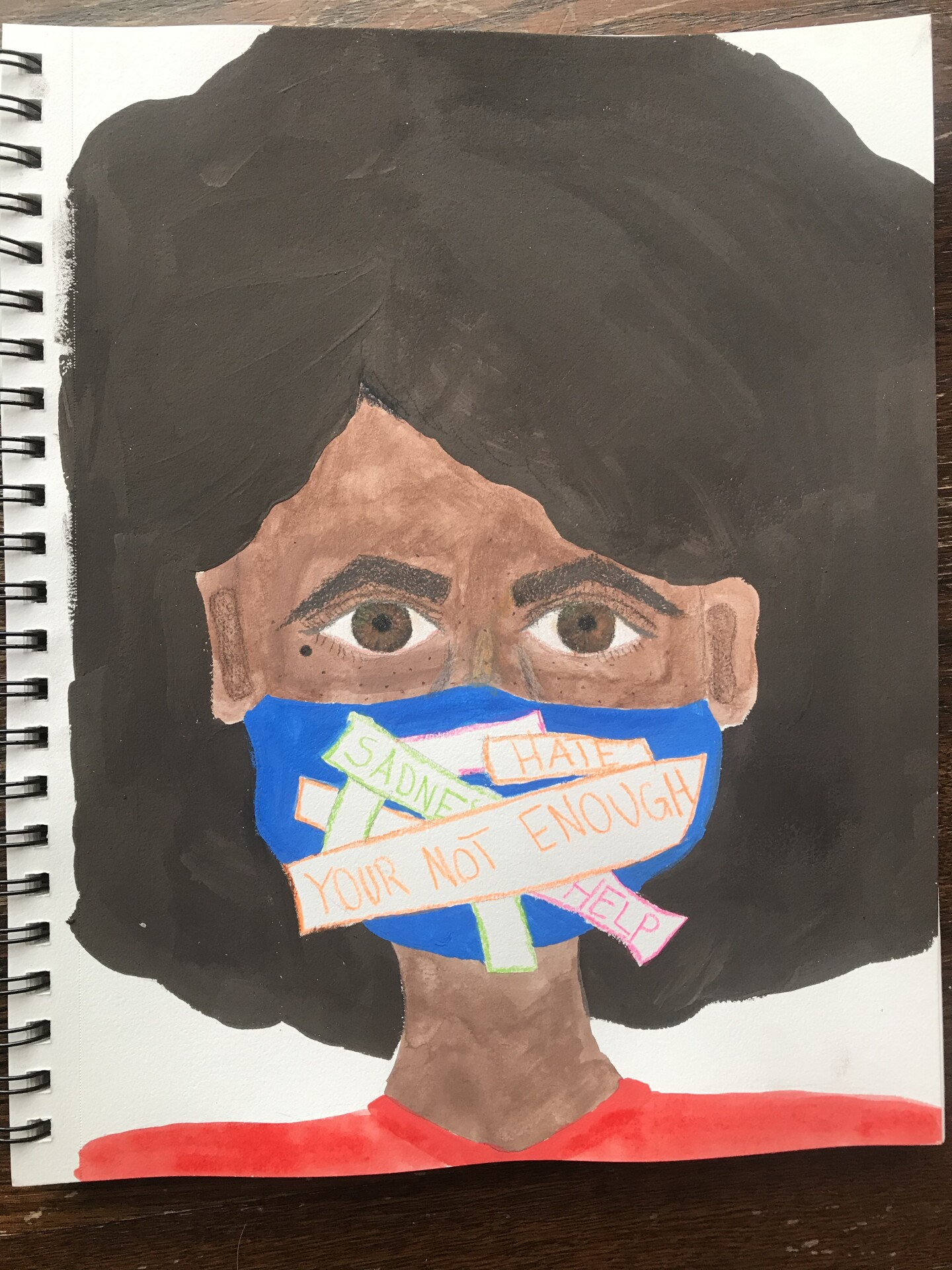 """A young woman of color wears a pandemic face mask with messages that read """"You're Not Enough,"""" """"Hate"""" and """"Sadness."""""""