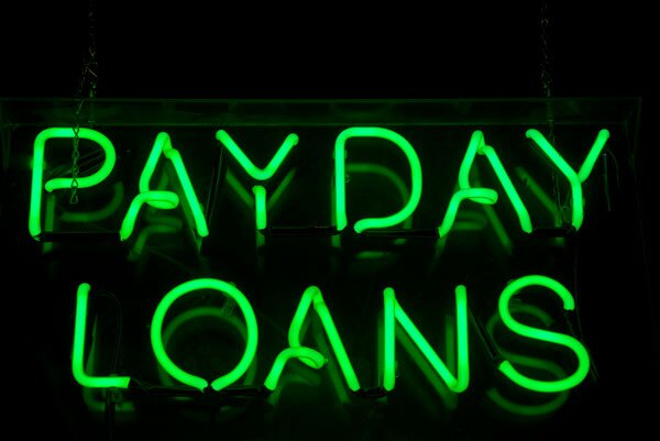 Neon green sign advertising payday loans.   iStock