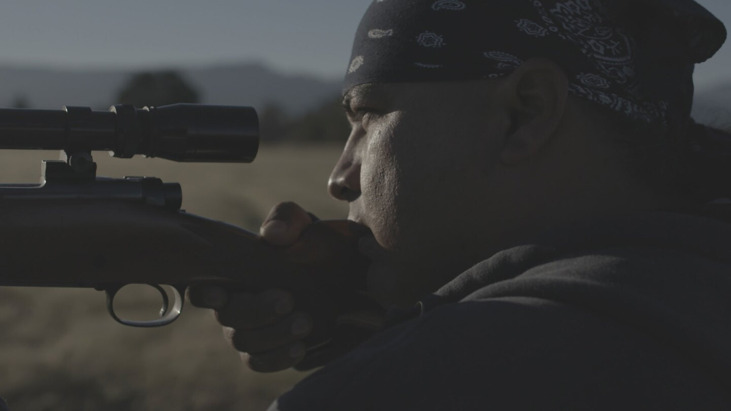 "Ray Alvarez looking into the iron sights of his rifle while hunting near the Pit River. | Still from ""Tending Nature"""