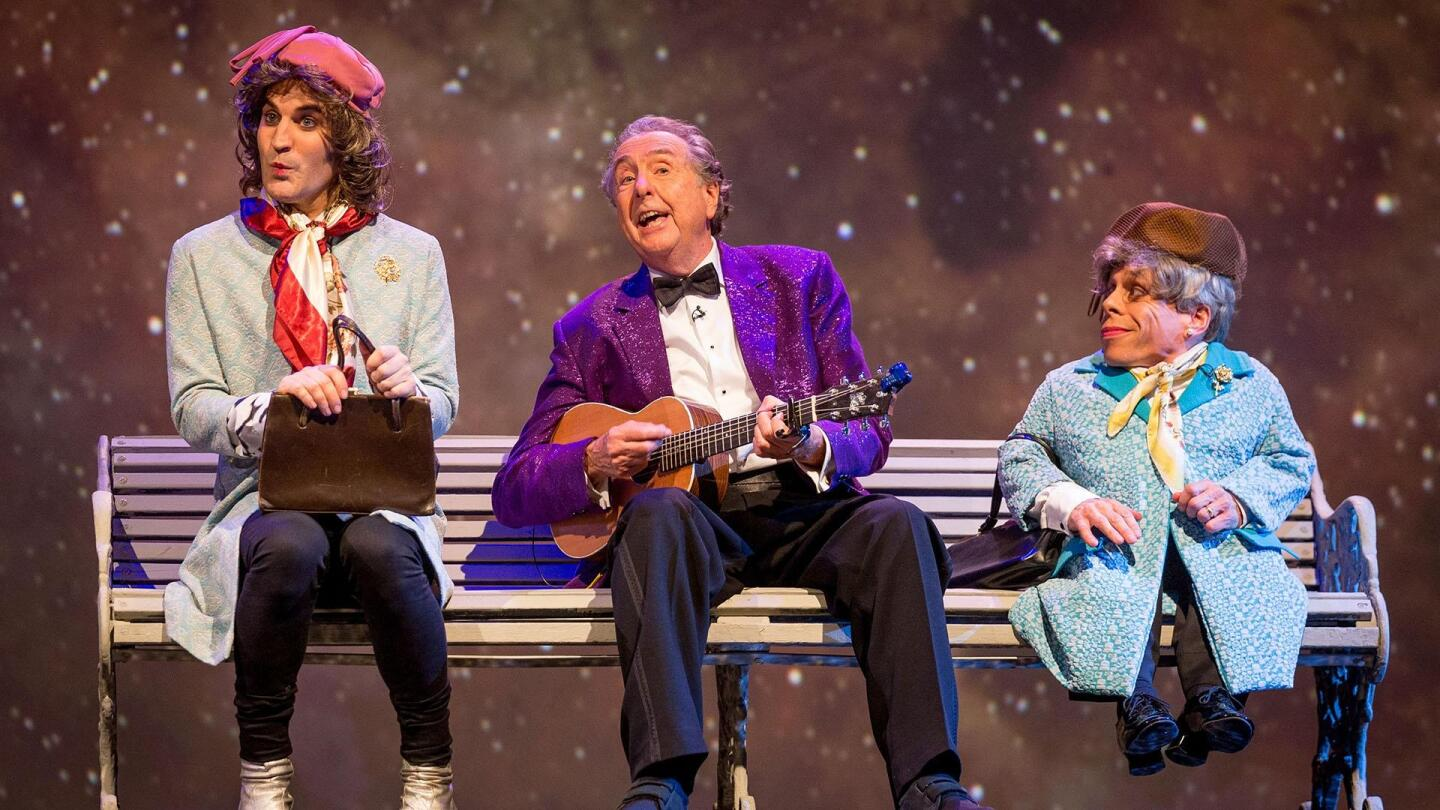 Noel Fielding, Eric Idle and Warwick Davis sit on a bench on stage.