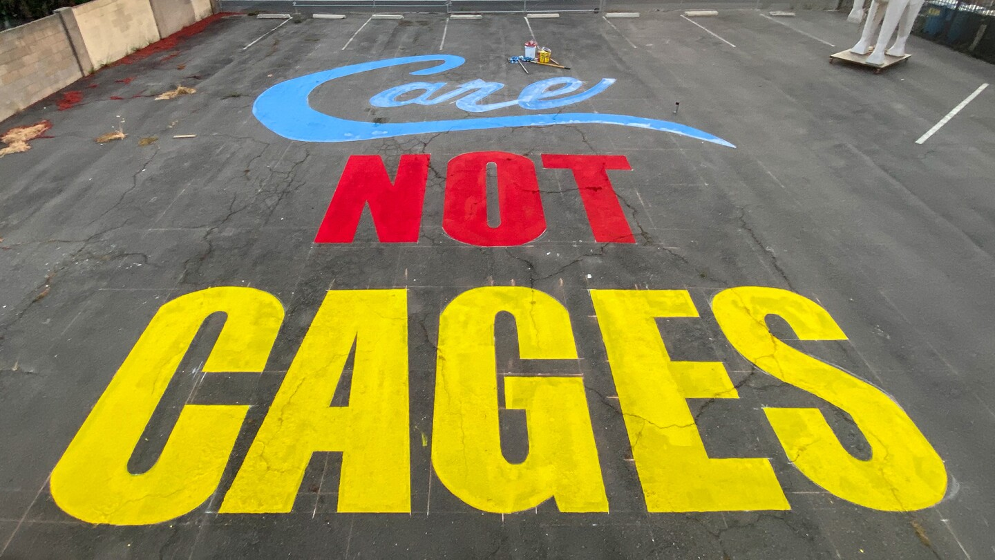 """""""Care Not Cages"""" painted on Crenshaw Dairy Mart grounds 