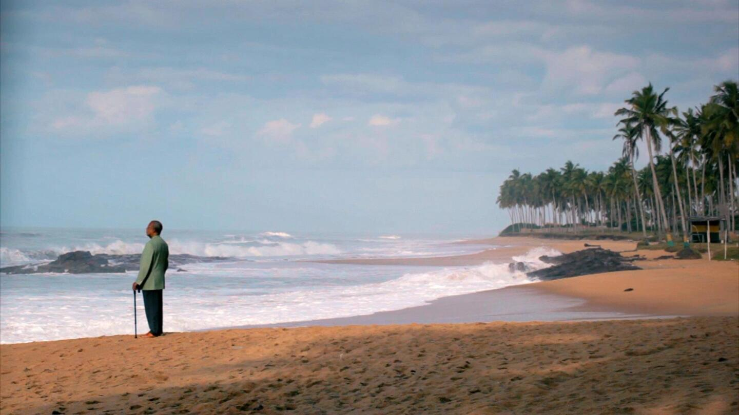 "A man holding a cane stands by an ocean. | ""Africa's Great Civilizations: The Atlantic Age"""
