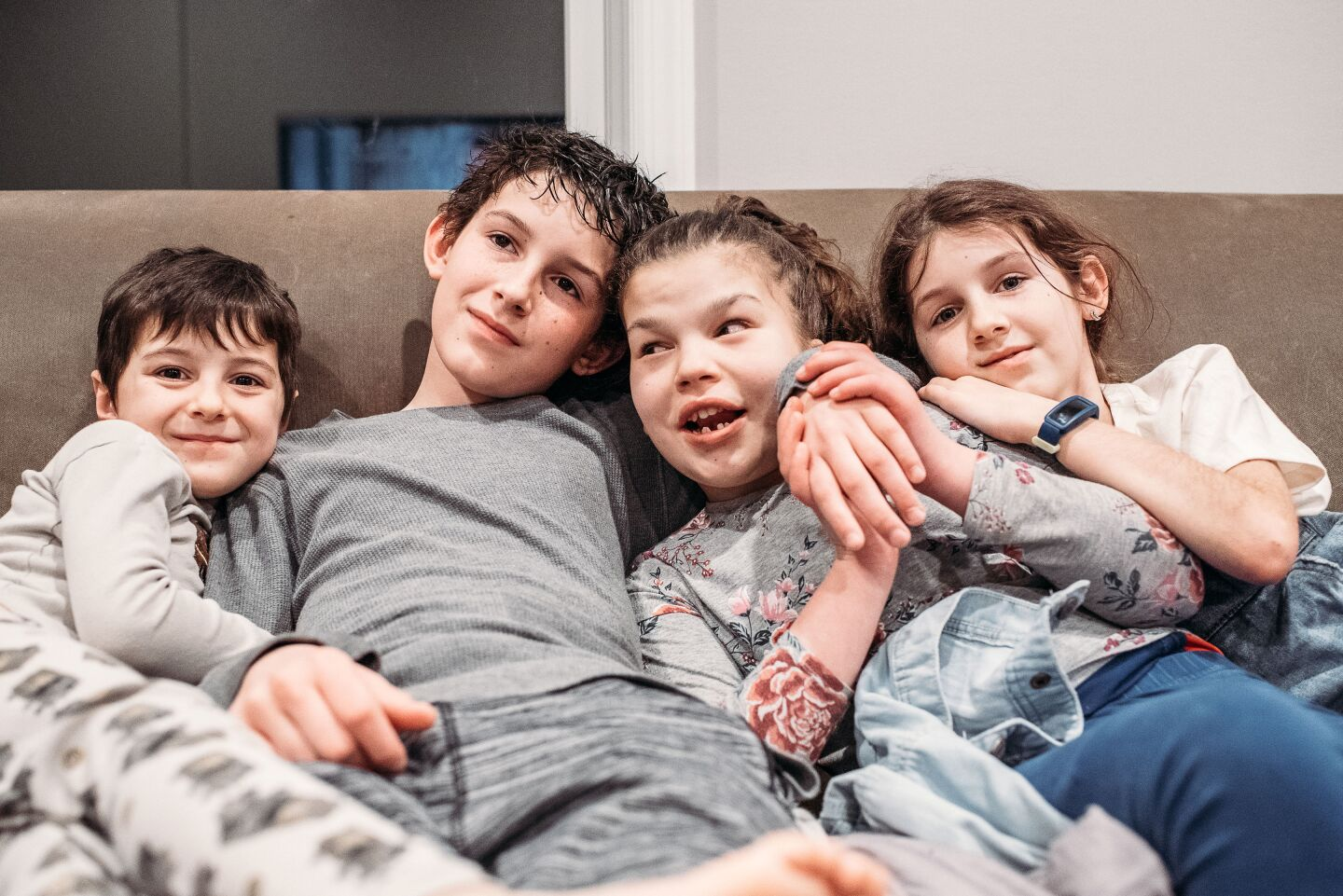 Four children hugging in the sofa