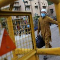 A man wearing a protective mask walks to board a bus that will take him to a quarantine facility, amid concerns about the spread of coronavirus disease (COVID-19), in Nizamuddin area of New Delhi, India, March 30, 2020.   REUTERS/Danish Siddiqui