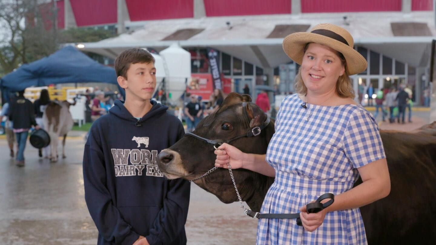 A woman holds onto the reins of a cow with a teenage boy next to her at the World Dairy Expo.