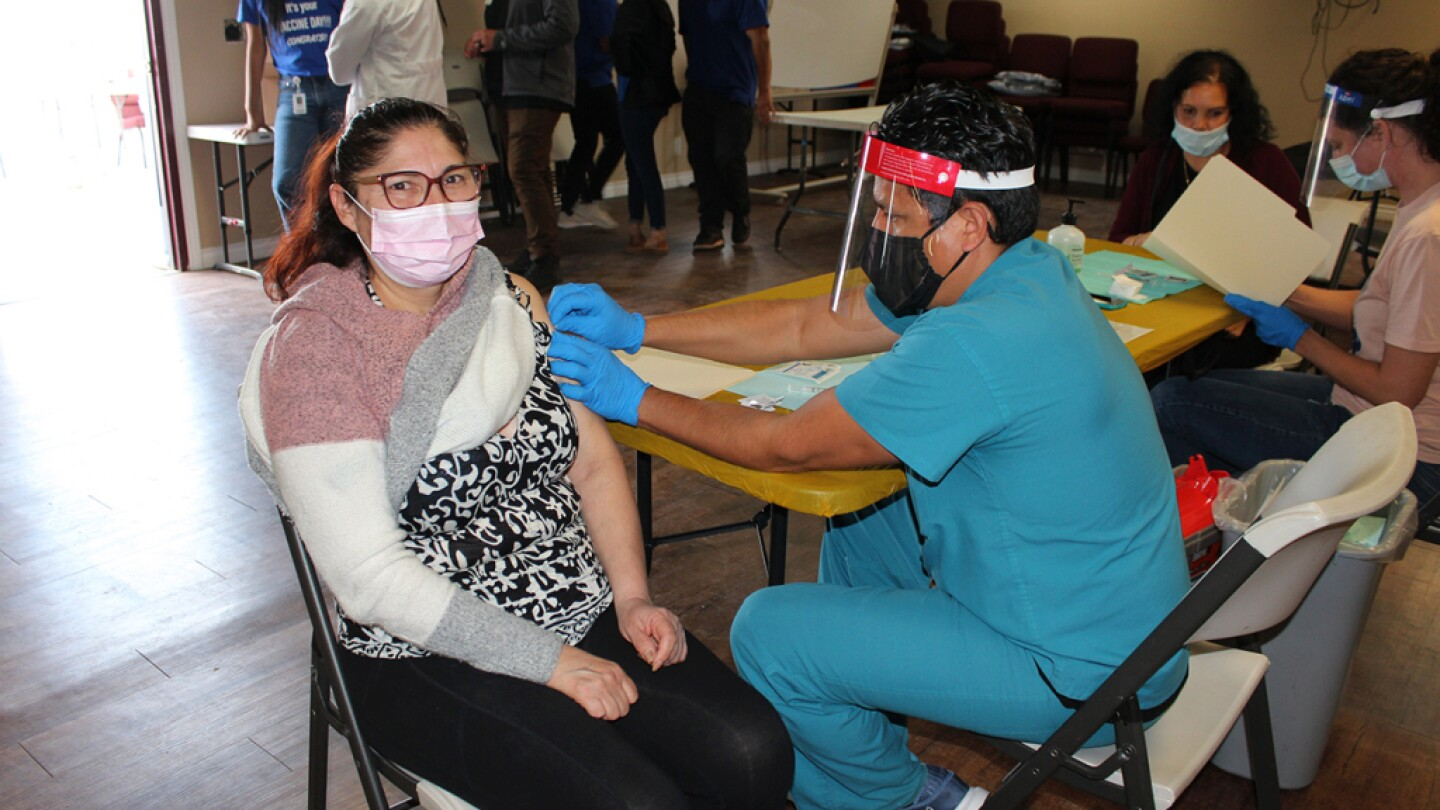 A woman wearing a pink face mask is getting a vaccine administered to her at a clinic. She's receiving the vaccine from a man wearing teal blue scrubs, a black face mask, a clear face shield and bright blue medical gloves.