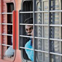 A migrant worker, who was stranded in the western state of Gujarat due to a lockdown imposed by the government to prevent the spread of the coronavirus disease (COVID-19), looks out from a window of a train that will take him to his home state.