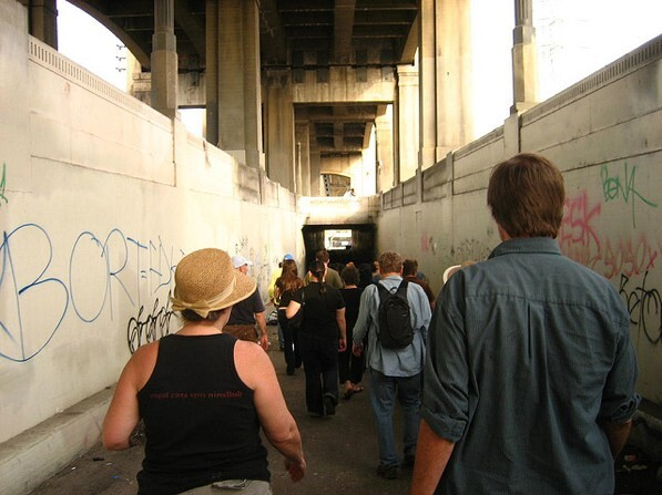 A group heads into a tunnel leading to a section of the L.A. River under the 6th Street Bridge | Photo by Zach Behrens