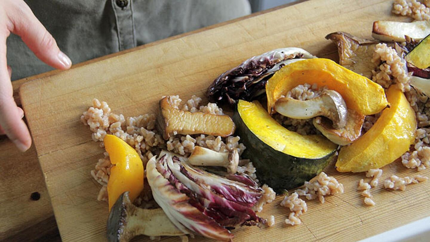 Mushrooms, farro, grains and other veggies on a cutting board.