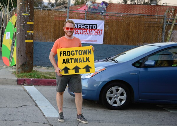 Volunteer Russell Horning grabs a Frogtown Artwalk sign and attempts to direct attendees to the designated parking lots and shuttles | Photo: George Villanueva